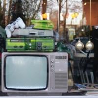 Une Xbox et une PlayStation posée sur une vieille télé à l'Arcade Hotel