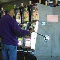 Un homme jouant au bandit manchot dans un casino