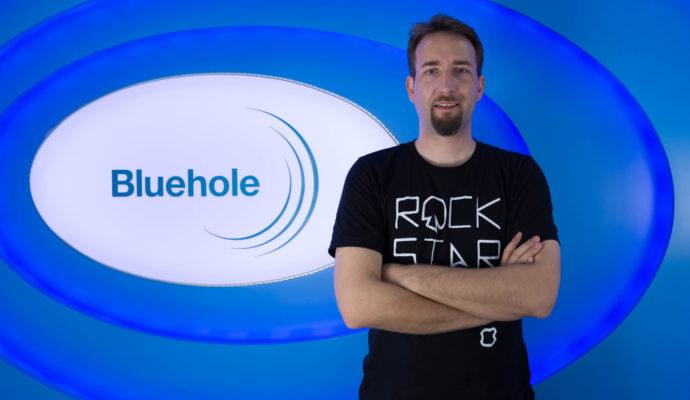Brendan Green, créateur de PlayerUnknown's Battlegrounds, devant le logo Bluehole